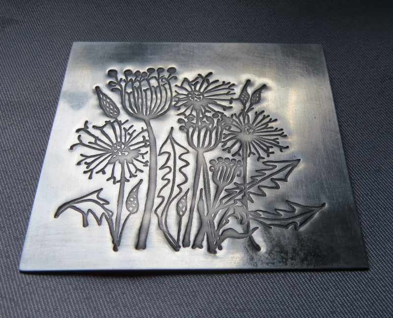 Pewter embossed coaster with antiqued satin finish & cork base. Pattern 2 / dandelions. Dimensions :- Approx. 9cm x 9cm