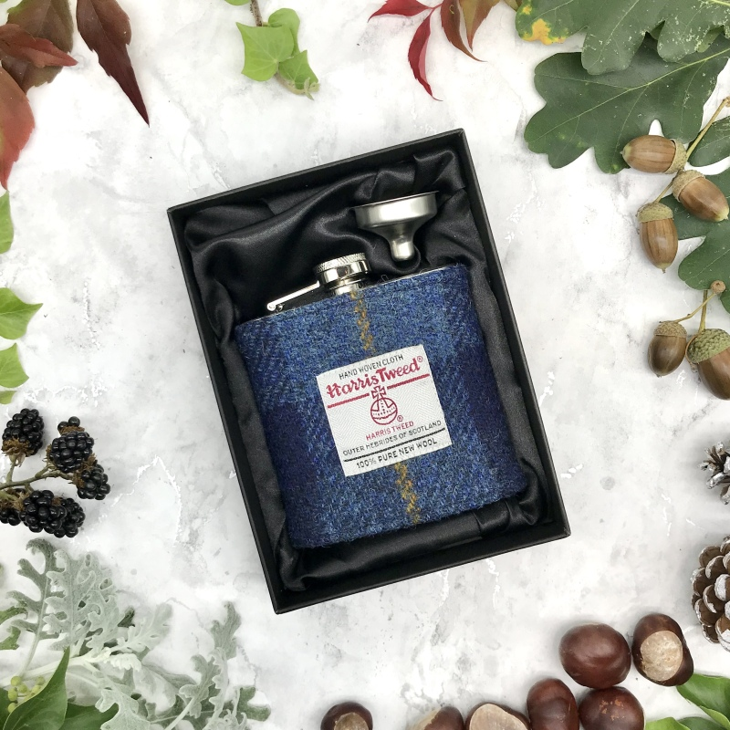 """6oz hip flask in stainless steel stands 4.25"""" (11cm) 1.75"""" high 4"""" (10cm) wide x 1"""" deep (2.5cm). Wrapped in Harris Tweed® sleeve 3.25"""" wide (8cm).   Comes in a black silk lined gift box with a funnel for ease of filling."""