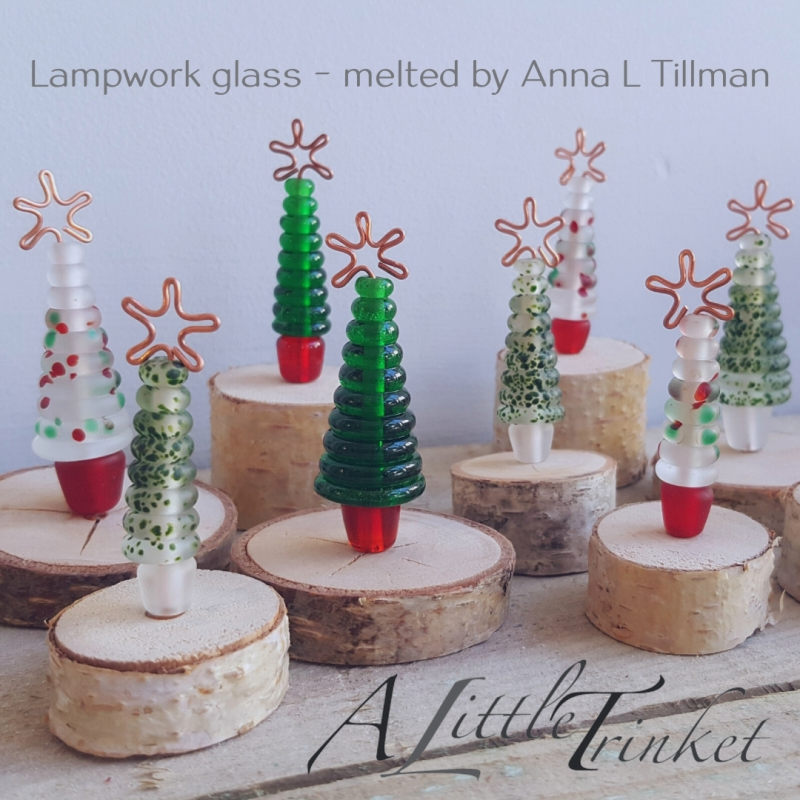 These mini Christmas trees are handmade by Anna in the A little Trinket Workshop. The tree (and its little pot) is lampwork glass, shaped and decorated in a gas flame. The tree is finished with a copper star & stands on a wooden plinth