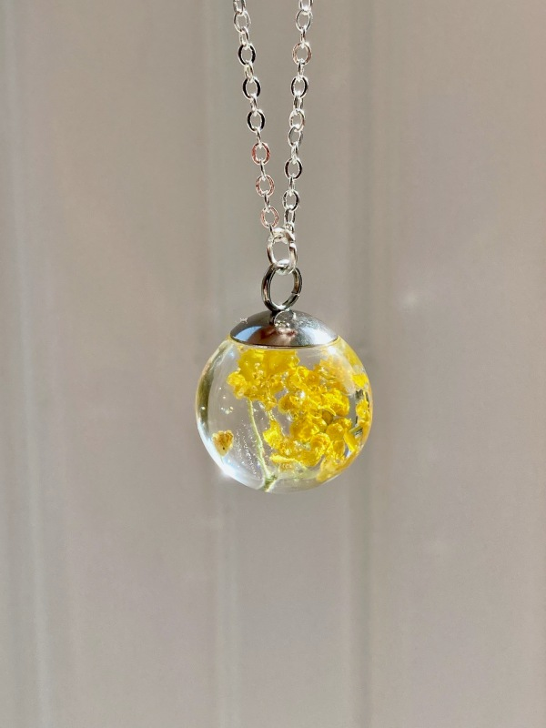 Resin Sphere Necklace containing a cluster of real, golden basket flowers