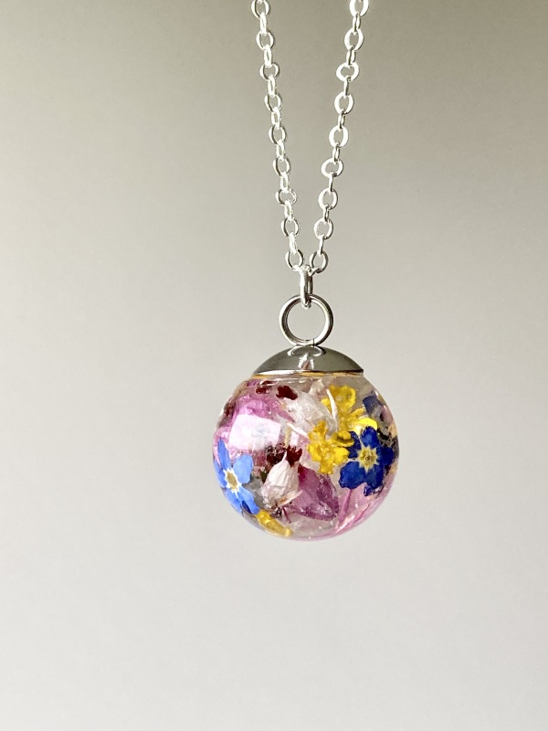 Resin sphere necklace containing real forget me nots, heather flowers golden basket flowers