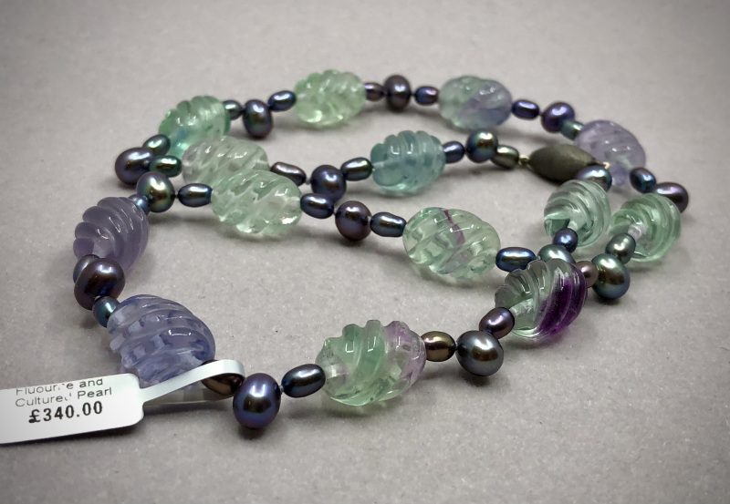 This stunning and unique design showcases the glorious violet and sea greens found in Rainbow Fluorite, teamed with peacock dyed cultured barrel and tear drop pearls.
