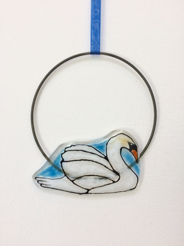 This fused glass Swan Circle Hanging is hand painted and I have used coloured glass powders.  The wire circle is approx 10cm diam.  It comes in tissue/bubble wrap and in a box.