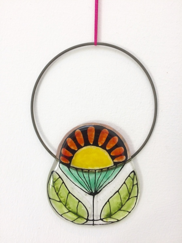This fused glass Flower Circle Hanging is hand painted and I have used coloured glass powders.  The wire circle is approx 10cm diam.  It comes in tissue/bubble wrap and in a box.