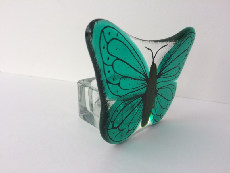 This Painted Teal Green butterfly T-Light Candle Holder is made with a fused and painted panel with a glass T-Light holder securely attached to the back of the panel.  The dimentions are approx. 11.5cm wide x 8cm tall and 6cm deep.