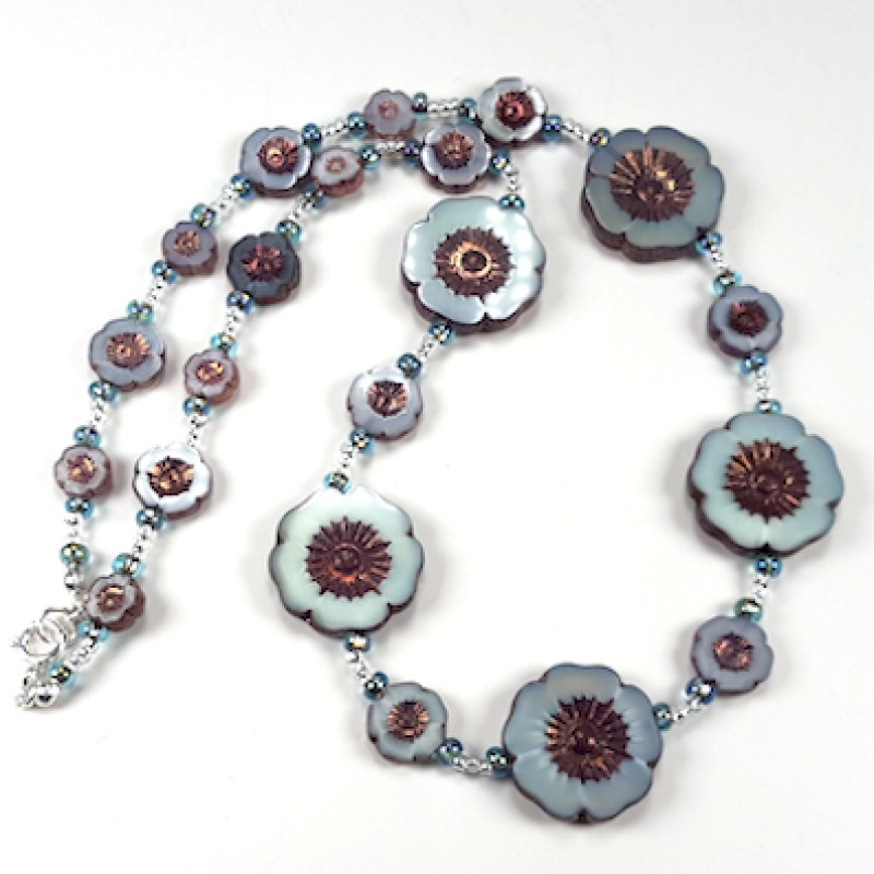 This gorgeous necklace made of Czech glass cut into flower shapes is a mixture of aqua/grey shades with a bronze effect at the centre of the flower and edges.  Length 51cm. With sterling silver findings and name tag.