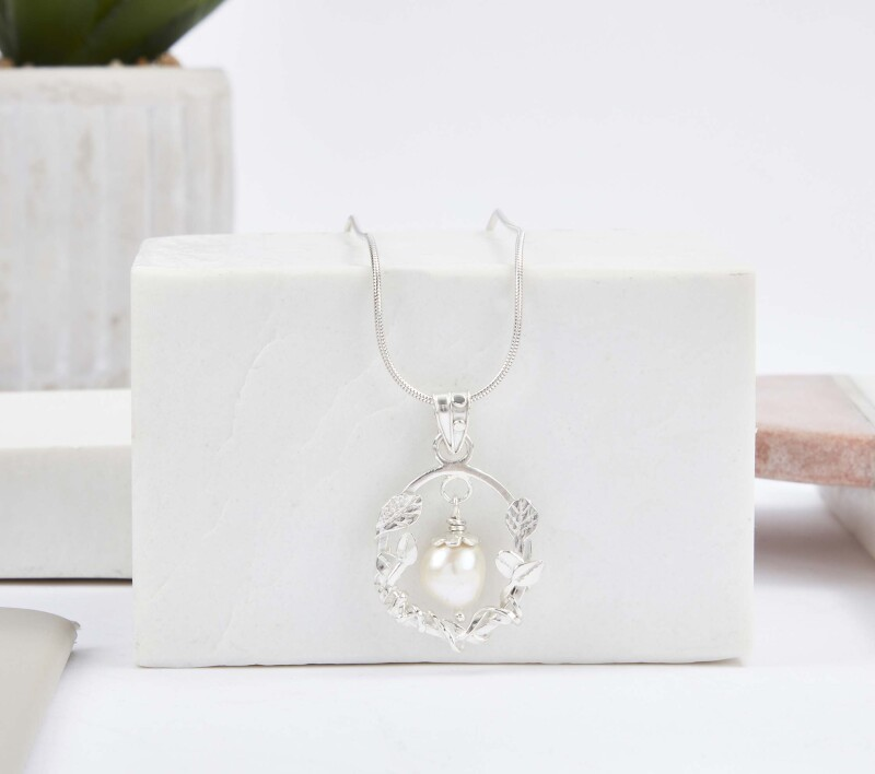 Tiny leaves and tendrils frame a dangling freshwater pearl. Argentium silver.