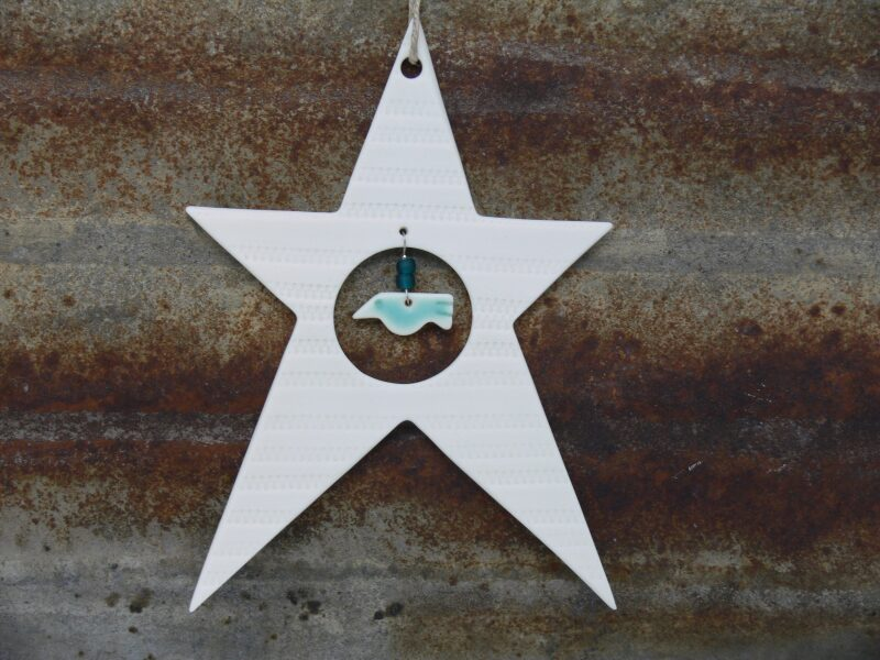 Hand rolled and cut porcelain star. The star has a delicate pattern impressed into the clay and has my characteristic hanging bird. The star is slightly larger than my other decorations 12 cm long/9 cm wide. Each decoration comes boxed.