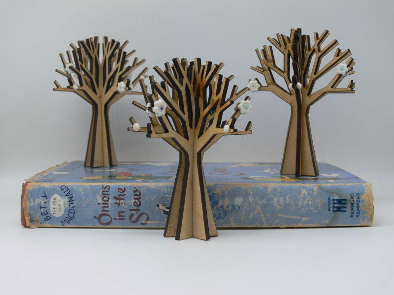 A small decorative tree made from MDF & decorated with porcelain flowers & buds. The tree is 10cm tall.