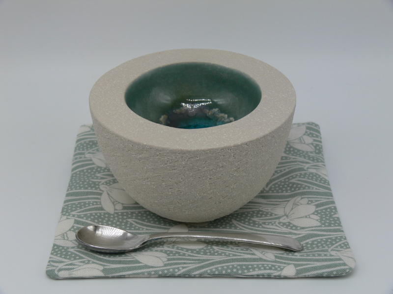 A round double walled coil-built pot made from a white gritty stoneware clay. The outside of the pot is left unglazed and textured, the inside glazed and decorated with glass. Each pot comes boxed with a fabric coaster and vintage condiment spoon.