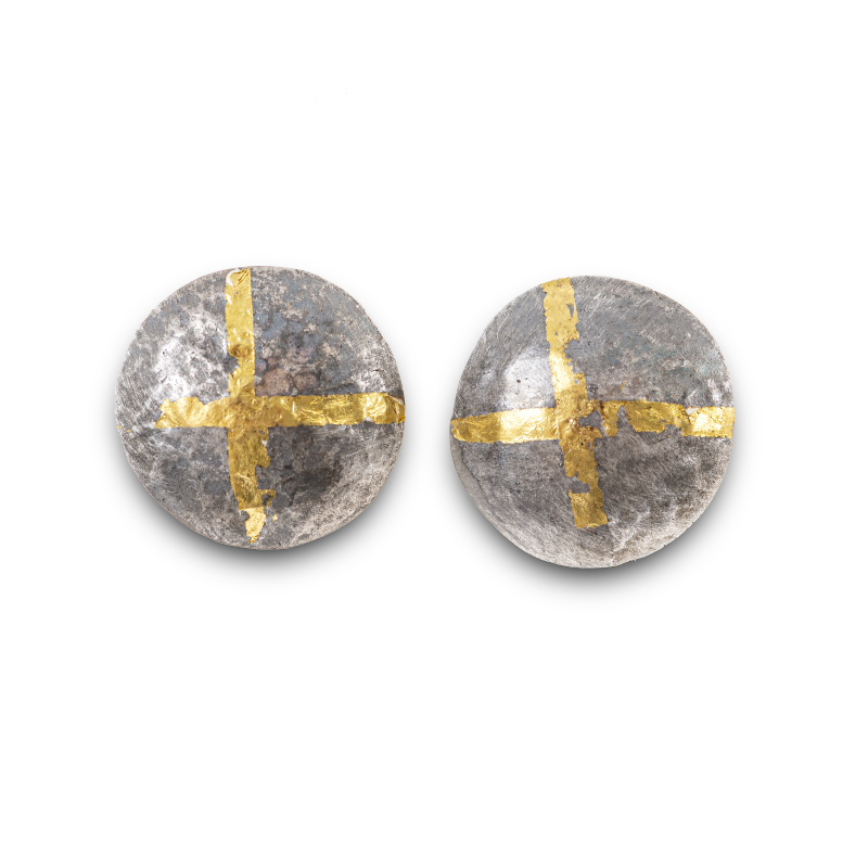 Handcrafted silver stud earrings have been oxidised to enhance the texture and the 24-carat gold cross