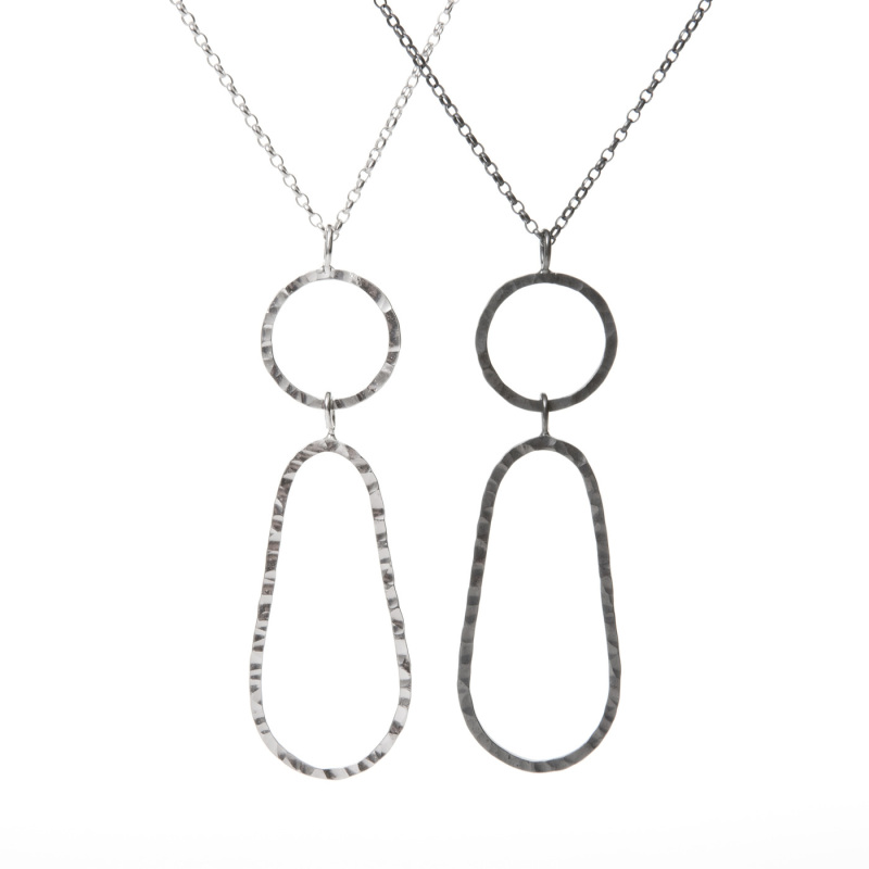 This simple long drop pendant looks great over a variety of clothing. There is a choice of colours, silver stands out over dark clothing and the oxidised version works well over light clothes.